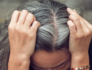 young lady looking depressed about her greying hair